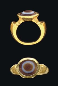 A ROMAN GOLD AND EYE AGATE FINGER RING   CIRCA 2ND-3RD CENTURY A.D.   The hollow hoop flat on the interior, bevelled on the exterior, expanding to the notched shoulders, the high hexagonal bezel set with a bevelled oval eye agate