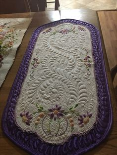 Vintage linen overlaid on purple satin and quilted.