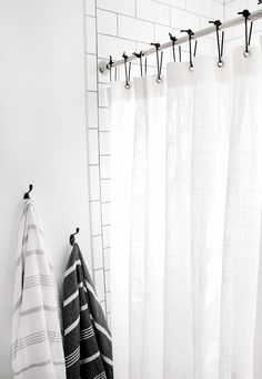 white shower curtain black hooks minimal bathroom