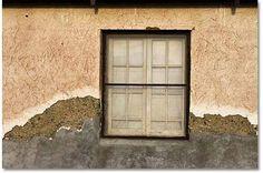 A curtained window hides the interior of this still-used cabin in Ballarat. - copyright Lara Hartley - DesertUSA
