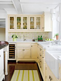 Buttercream + White + Vintage Green Evoking nostalgia, this kitchen recalls simpler times with its buttercream-colored cabinets and hand-stenciled pale green and white tile backsplash. A deep farmhouse sink and white marble countertop further impress the feel of a vintage bake shop. Green accents come in cottage pieces: a pitcher of hydrangeas, bottled water, and a striped cotton rug.