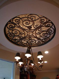 The ornamental ceiling medallion looks like it is made of iron but it is actually custom made from a composite wood material - faux iron. material Faux Wrought Iron Ceiling Medallion Over Chandelier. Ceiling Decor, Ceiling Design, Ceiling Lighting, Foyer Lighting, Ceiling Detail, Accent Lighting, Wall Decor, Plafond Design, Wrought Iron Decor