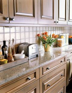 neutral tones, clear glass tiles - unify, brighten and seemingly enlarge a small kitchen :)