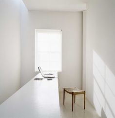 John Pawson minimalist workspace all white wooden stool shadows on the wall