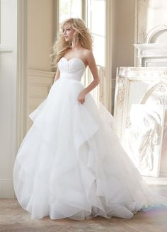Londyn Hayley Paige HP6358 Ivory strapless natural waist bridal ball gown with silk radzmir crossover bodice, full tulle skirt with horsehair flounces and chapel train. Shown with matching horsehair v
