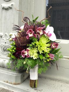 Unique bridal bouquet with pincushion protea, phalenopsis orchids, cymbidium orchids, mums, hypericum berries, mini eucalyptus, fern curls, ming fern, feathered eucalyptus, and ruskus.