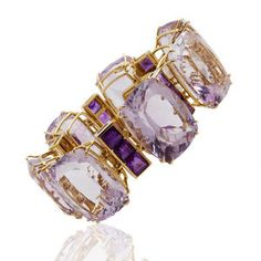 An amethyst bracelet by Tony  Duquette designed as seven cushion-shaped light purple amethysts each with square-cut amethyst three-stone spacers; signed Tony Duquette; mounted in 18kt yellow gold.  Sold at auction for 11,250 USD.