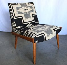 The Ansel Chair is a sleek and simple, authentic Mid Century piece, beautifully upholstered in blanket-weight wool from Pendleton's Portland Collection.  The wool is soft, durable, and iconic with very Navajo-influenced design.  The color palette is black and bone white.  Large-scale pattern has been meticulously aligned for a seamless look and antique brass nailhead trim finishes the back.