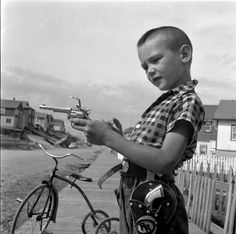 Boy Shooting Toy Gun, Flin Flon, Manitoba. 1954. [Rosemary Gilliat Eaton] MIKAN# 4306633