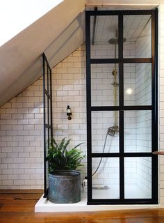 """The cottage only had one bathroom when Barry bought it, so he """"... ran the plumbing straight up into [one of the bedrooms] and installed the shower, sink and toilet."""" Brass finishes and a streamlined shower screen give this one the """"gentlemen's smoking room"""" vibe Barry hoped for."""