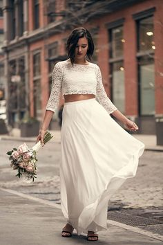 With lace three-quarter sleeves, this two-piece wedding dress crop top pairs beautifully with a white maxi skirt. Available at David's Bridal. Photo by Frankie Marin.