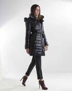 Plumífero largo de mujer acolchado negro, capucha desmontable y pieza extraíble de pelo de conejo, cinturón y cierre con cremallera y broches.
