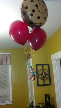 Elf on shelf hanging from balloons.