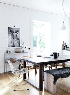 Bertoia wire chair. Bench seat. Black sheepskin. Wishbone chairs. White paneling.
