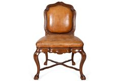 'Solid walnut frame with a lightly distressed and aged finish. Drop-in upholstered leather back and seat within wood frame.'