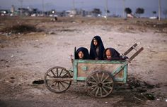 Afghan refugee boys wrap themselves with blankets to avoid the evening cold while sitting in a wooden cart as they look at a group of girls playing hopscotch in a field on the outskirts of Islamabad, Pakistan, on November 30, 2012. (AP Photo/Muhammed Muheisen) via The Atlantic