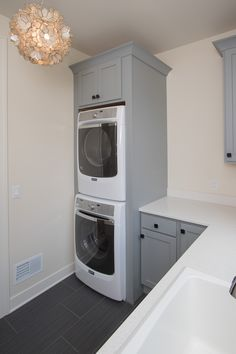 Laundry Room: ceramic tile floors, painted cabinets and built-ins, stacked washer / dryer, quartz countertops