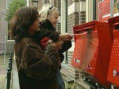 Een kind doet een zelfgemaakte kerstkaart op de post. Je ziet wat er met een kaart gebeurt nadat je die in de brievenbus hebt gegooid.
