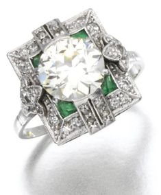 Art Deco emerald and diamond ring, circa 1910. The center diamond - a circular cut stone of 2.07 carats -  is set within a millegrain surround of circular and single cut rose diamonds and accented by emerald details. Via Diamonds in the Library.