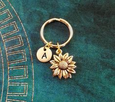 This listing is for a personalized sunflower pendant necklace with a hand-stamped initial charm. Youll be able to choose your initial at checkout, as well as chain length and style. :) Keyrings and bangle bracelets are also available, just choose that as your style from the drop-down menu.