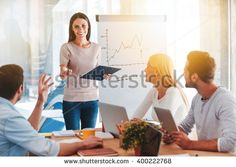 Discussing new business ideas. Cheerful young woman standing near whiteboard and smiling while her colleagues sitting at the desk
