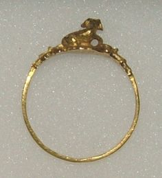 Love ring,  16th century.  Gold ring, the bezel in the form of a dog couchant, the shoulders of the hoop worked into leafage.