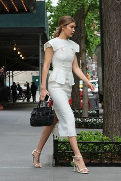 Gigi in a white Roland Mouret top and skirt, and elegant Stuart Weitzman