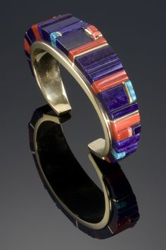18k gold bracelet inlayed with coral, sugilite, and turquoise by Charles Loloma. Measures 5 1/4″ with a 1″ opening. 3/4″ width.