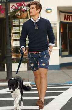 Shop this look on Lookastic:  http://lookastic.com/men/looks/long-sleeve-shirt-cable-sweater-belt-shorts-bracelet-loafers/10408  — White Vertical Striped Long Sleeve Shirt  — Navy Cable Sweater  — Brown Woven Leather Belt  — Navy Print Shorts  — Beige Woven Bracelet  — Brown Leather Loafers