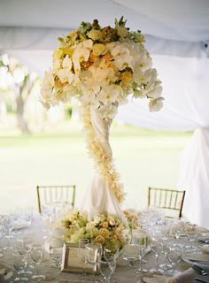 The draping around the vase puts this centrepiece in a completely different class.  Top that with the flowers used and it is as lavish as you can get.