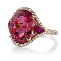 A glorious and finely saturated oval pink tourmaline is kissed by sweet pear-shaped rubies on either side on this 18k rose gold and diamond ring by Omi Privé