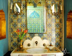 Spanish influenced bathroom - love the tiles around the mirror!