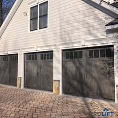 The appearance of carriage house garage doors can be deceiving. From a distance, they mimic swing-out barn doors when ACTUALLY they're modern overhead doors that go up and down. But will a carriage house garage door look right on your home? Grey Garage Doors, Side Hinged Garage Doors, Faux Wood Garage Door, Carriage House Garage Doors, Garage Door Panels, Garage Door Styles, Garage Door Design, House Doors, Barn Garage
