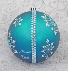 Margot Clark created this large, turquoise ornament with a White 3D snowflake texture painted design and added rhinestone bling. The color changes depending on the lighting. Each ornament created is a one-of-a-kind. The texture medium and paint brush I use to paint the ornaments were both created to my specifications. My signature M is located on the bottom of the ornament. Gift boxed. Measures 3 1/2 x 3 1/2 Ornament weight is 2 ounces.