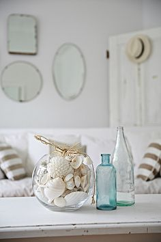 another day another beach cottage-- shells, straw hat, mirrors, blue bottles, white furniture---lovely!