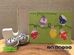Colorful String of Lights. Lawn Fawn Merry Messages Photopolymer, Lawn Fawn String of Lights Lawn Cuts, Hero Arts Silver Embossing Powder, Pretty Pink Posh Raspberry, Pansy Purple, Lemon Drop, Cobalt and Pumpkin Sequins.