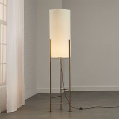 Shop Haus White Floor Lamp.   Inspired by rooftop water tanks in warehouse neighborhoods across the U. S. , this sculptural lamp rises from plated brass frame to cylindrical linen shade in svelte, modern shape.