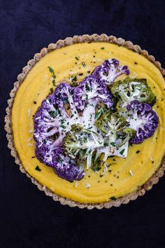 A lusciously creamy cauliflower tart recipe on a fresh garlic and herb gluten-free almond-based crust, topped with thinly sliced veggies, making for a very sensationally savory and comforting tart situation! #cauliflowertart #glutenfreetart #savorytartrecipe