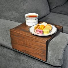 "A handmade armrest table for your sofa, couch or recliner. Perfect for storing your drinks, food, laptop and more! Tired of losing your TV remote, spilling your beverages or dropping your plate? We got you covered, our armrest table will save you time, money and headaches. The armrest table was designed with side bumpers to prevent items from falling off (see photos) and is made from durable oak wood which is easy to clean. The dimensions of the armrest table are 10"" Long x 5"" High x 7""…"