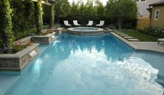 rectangular pool with circular spa and lounge chairs with vine-covered pillars