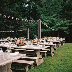 Wooden benches at the reception | Blackberry Farm Wedding | Floral basket centerpieces with pretty glassware