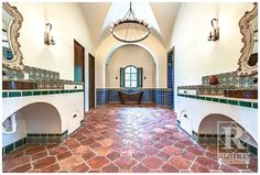 Check out the epic awesomeness of a Spanish Colonial style home in this bathroom! Antique Saltillo terracotta flooring is tied together with painted Talavera tiles and a romantic HUGE copper bathtub. Ornate mirrors and lighting add some sparkle to this rustic space. #stylerusticotile #rustic #spanishcolonial #colonial #oldworld #mexicantile #terracotta #copper #bathroom #style #hacienda #diy #homedecor #interiors #flooring