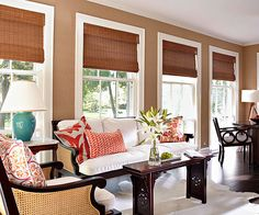 Establish Zones - Long and fairly narrow, this sunroom could have easily become a mishmash of furniture and materials. Instead, the homeowner divided it, almost in half, creating living and dining zones in this tropical-influenced space. Dark stain and a repeating use of wicker help to coordinate the furniture, and textural wallpaper, as well as patterned pillows, add pretty pops of color.