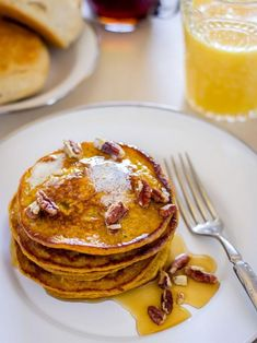 Pumpkin Spice Pancakes Soaked in Syrup and Topped With Chopped Pecans