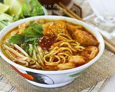 Curry Laksa, a tasty and spicy Malaysian coconut based curried noodle soup topped with shredded chicken, shrimps, fried tofu, and bean sprouts.   Food to gladden the heart at RotiNRice.com