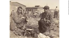 Caption: Two survivors prepare food outside the barracks. The man on the right is thought to be Jean (Johnny) Voste, born in Belgian Congo -- the only black prisoner in Dachau.  Photo Credit: United States Holocaust Memorial Museum, courtesy of Frank Manucci  Date: May 1945