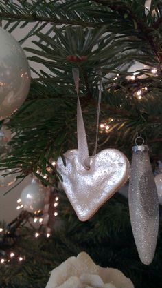 Van brooddeeg eigen gemaakte kerst versiering, zilver geschilderde hartjes. Maak het gaatje erin voordat t de oven in gaat.