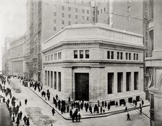 Photograph taken in 1914 by Irving Underhill of 23 Wall Street at Broad in New York City shows the J.P. Morgan & Co. building with many people on the street, some looking directly into the camera.