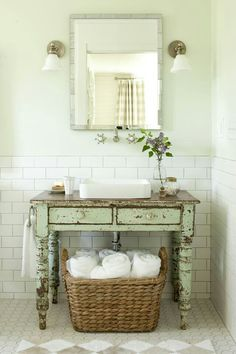 Adding a vintage-inspired vanity gives this bathroom a rustic vibe. Love the big basket of towels