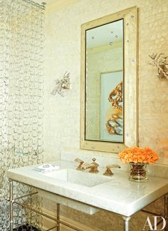 In the powder room, a Stark mother-of-pearl wall covering replaced the previous owner's damask wallpaper; the privacy curtain is composed of glass links from Global Views, the mirror is a customized Roger Thomas design for APF Munn, the Moth Design sconces are covered in Swarovski crystals, and the sink fittings are by Sherle Wagner International.